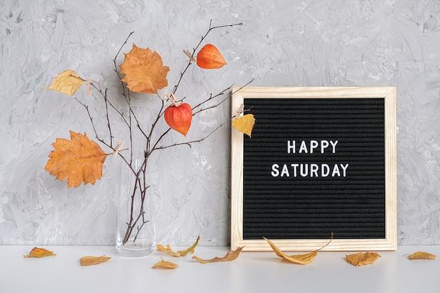 Texte du samedi heureux sur le carton noir et bouquet de branches à feuilles jaunes Photo Premium