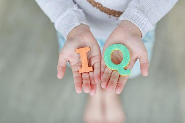 Texte en éponge de quotient intellectuel sur les mains d'un enfant Photo Premium