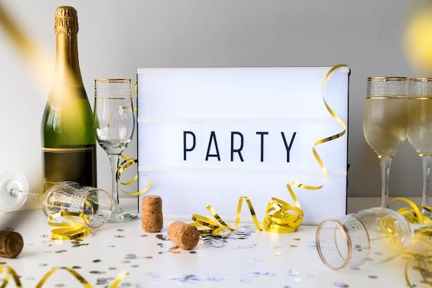 Texte de fête sur la boîte à lumière avec une bouteille de champagne et des objets de décoration Photo gratuit