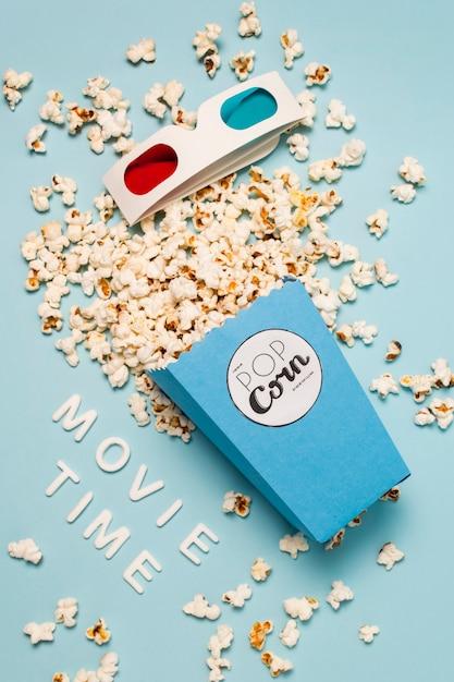 Texte de l'heure du film avec des popcorns renversés à partir de popcorns et des lunettes 3d sur fond bleu Photo gratuit