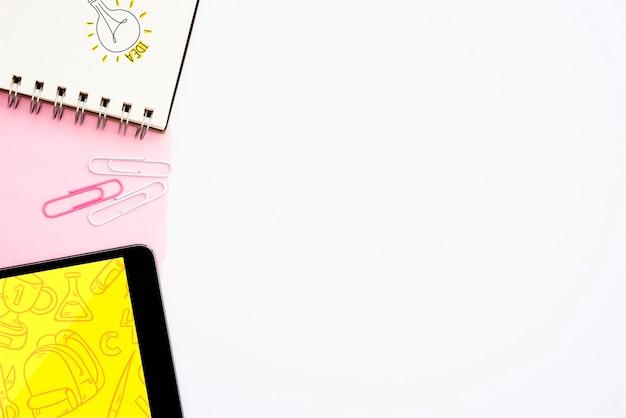 Texte d'idée et ampoule dessiné à la main sur le bloc-notes en spirale avec tablette numérique sur fond blanc Photo gratuit