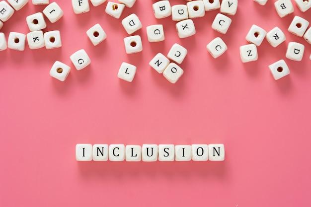 Texte D'inclusion Fabriqué à Partir De Cubes En Bois Sur Une Table Rose. Concept Social Inclusif. Mise à Plat. Photo Premium