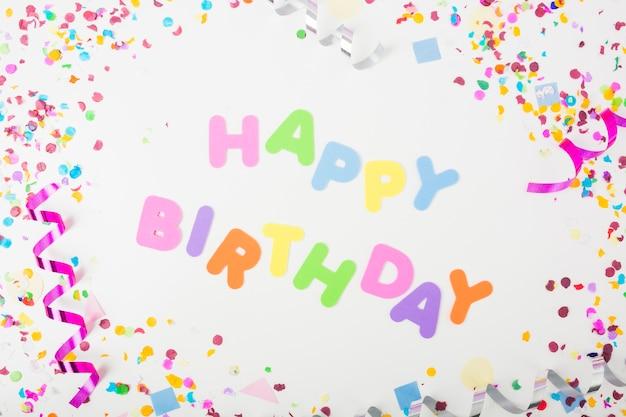 Texte de joyeux anniversaire avec des confettis et des serpentins de curling sur fond blanc Photo gratuit