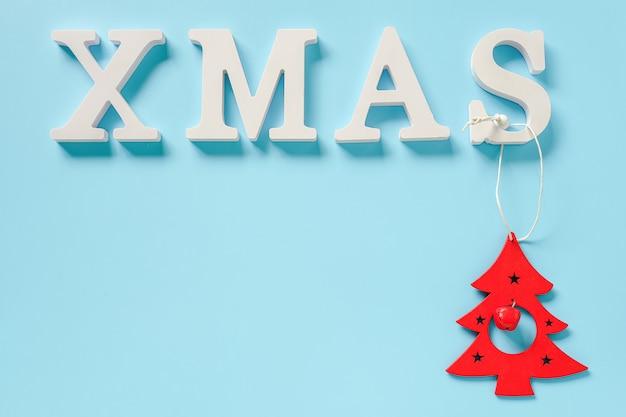 Texte noël de lettres blanches et jouet de décoration arbre de noël rouge sur fond bleu Photo Premium