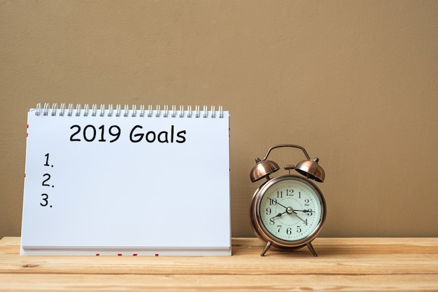 Texte des objectifs 2019 sur le bloc-notes et le réveil rétro sur la table et l'espace de copie Photo Premium