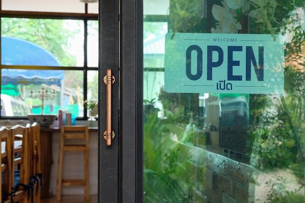 Texte Ouvert Sur Panneau De Porte Et Raccrocher Sur La Porte En Verre Du Café Photo Premium