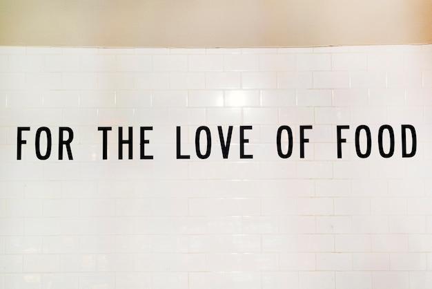 Texte pour l'amour de la nourriture sur un mur blanc Photo gratuit