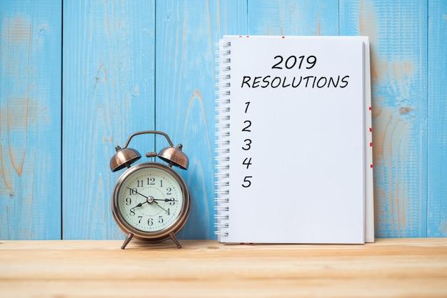 Texte des résolutions de 2019 sur un cahier et réveil rétro sur une table Photo Premium