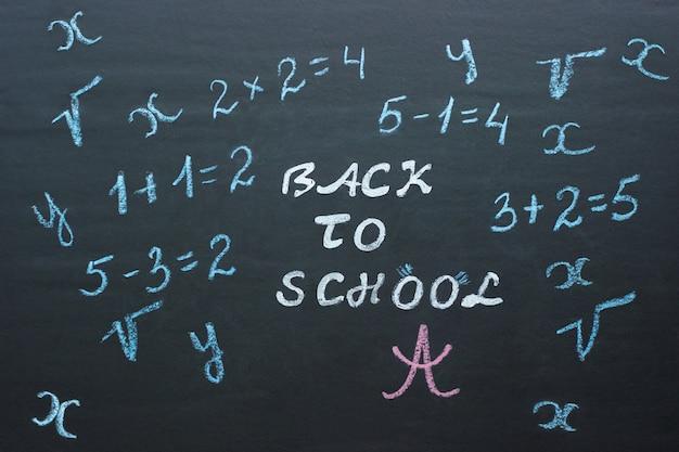 Texte retour à l'école et exemples mathématiques au tableau noir Photo Premium