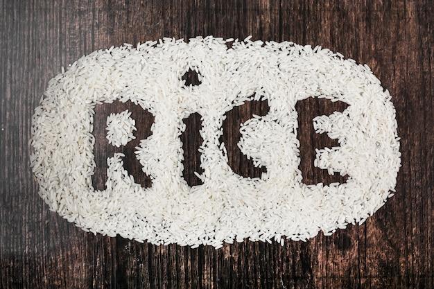 Texte de riz sur fond texturé en bois noir Photo gratuit