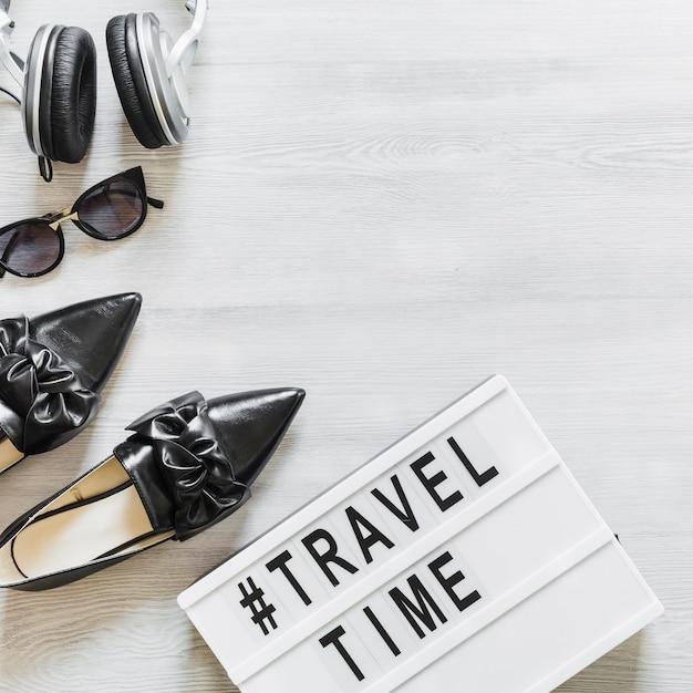 Texte de temps et de voyage avec des chaussures, des lunettes et un casque sur le bureau Photo gratuit