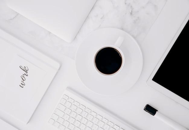 Texte de travail sur le journal; tablette numérique; tasse à café; clavier et marqueur noir sur le bureau blanc Photo gratuit