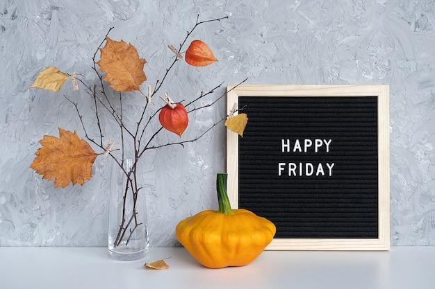 Texte de vendredi heureux sur le carton noir et bouquet de branches Photo Premium