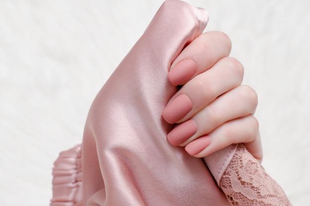 Textile satin rose pâle dans une main féminine. manucure de beauté. Photo Premium