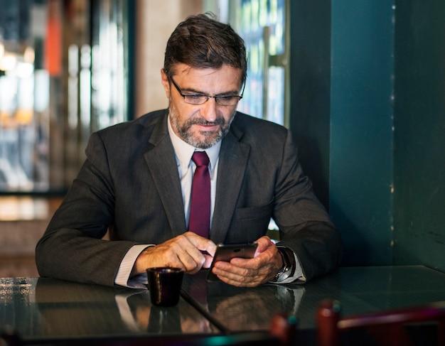 Textos homme d'affaires sur son téléphone portable Photo gratuit