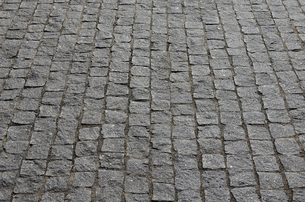 La texture de la dalle (pavés) de nombreuses petites pierres de forme carrée sous un soleil éclatant Photo Premium