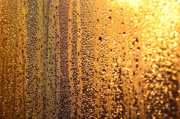 La texture du verre embué avec beaucoup de gouttes et de gouttes de condensation contre la lumière du soleil à l'aube Photo Premium