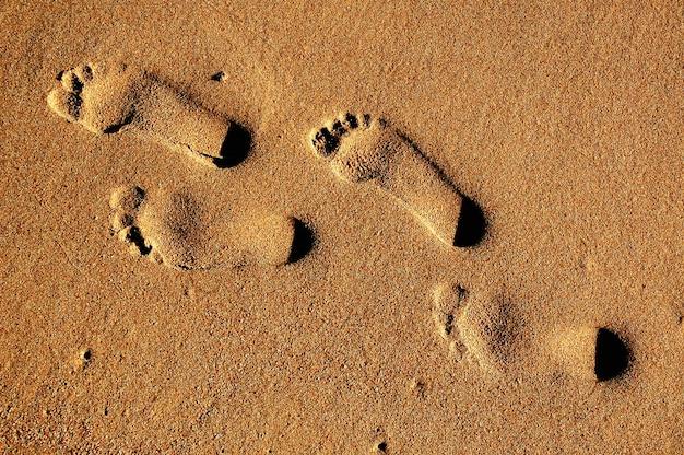 Texture de fond empreintes de pieds humains sur le sable près de l'eau sur la plage. Photo Premium