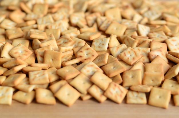 Texture de fond de petits carrés comestibles cuits de la pâte et saupoudrés de sel. beaucoup de biscuit salé Photo Premium
