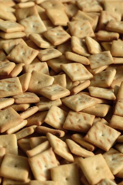 Texture de fond de petits carrés comestibles cuits de la pâte et saupoudrés de sel. Photo Premium