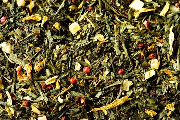 Texture de thé vert avec fleurs jaunes pétales séchées et poivron rouge. aliments. feuilles de plantes bio saines, thé de désintoxication. Photo Premium