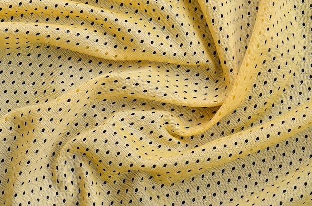 Texture de tissu de vêtements de sport jersey jaune et fond avec beaucoup de plis Photo Premium