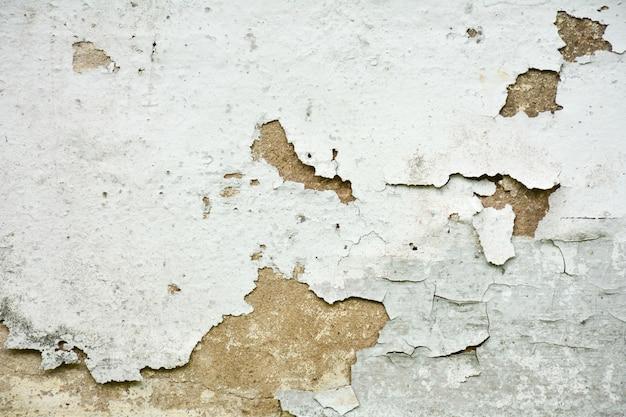 La texture de la vieille peinture blanche est ébréchée et fissurée au mur Photo Premium