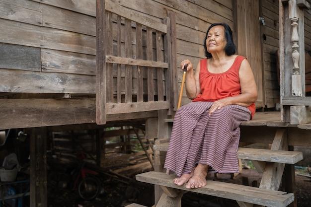 Thai Femme âgée En Col Rond Sans Manches Assis Seul Dans La Vieille Maison En Bois Photo Premium