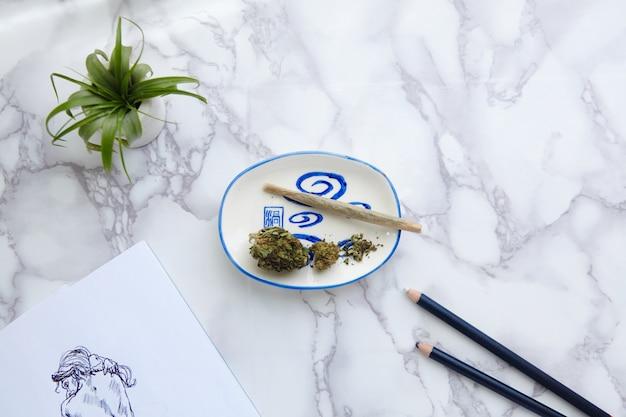 Thc Cbd Marijuana Joint Et Fleurs Sur Cendrier Avec Illustration Nue Sur Bloc-notes Photo gratuit