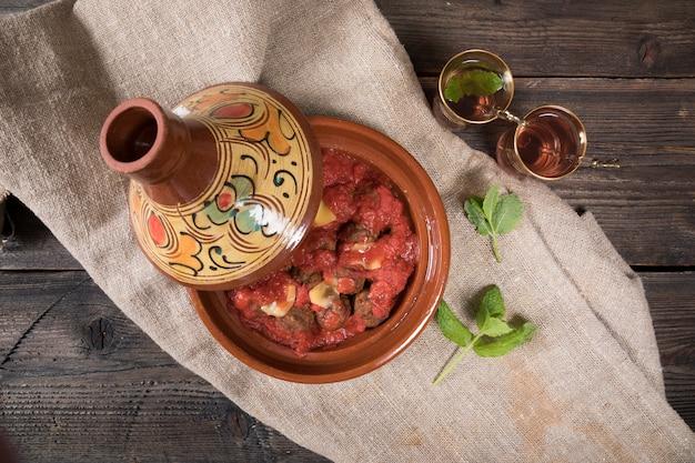 Thé arabe dans des verres avec de la viande en tajine Photo gratuit