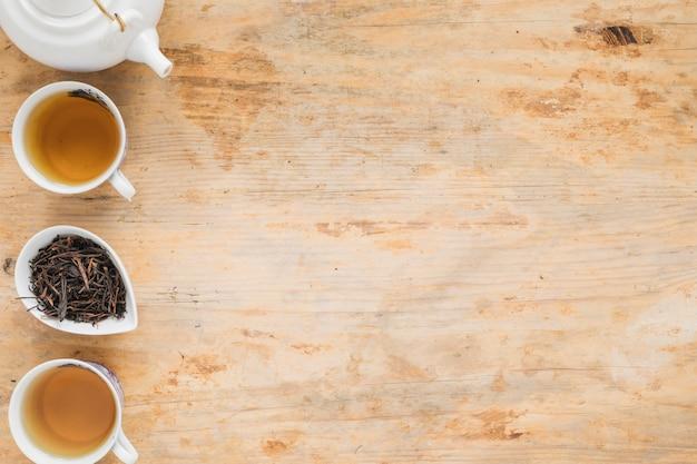 Thé au citron avec des feuilles de thé sèches et théière sur une table en bois Photo gratuit