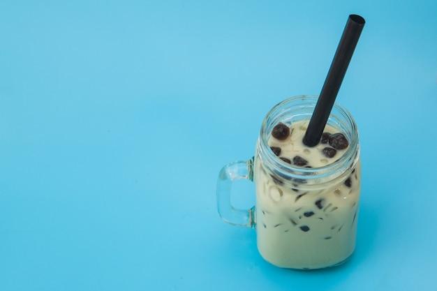 Thé au lait glacé avec bubble boba dans le bocal en verre sur fond bleu Photo Premium