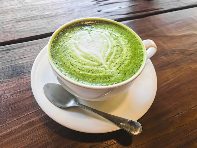 Le thé au lait vert matcha chaud avec du lait crémeux est un motif en forme de cœur Photo Premium