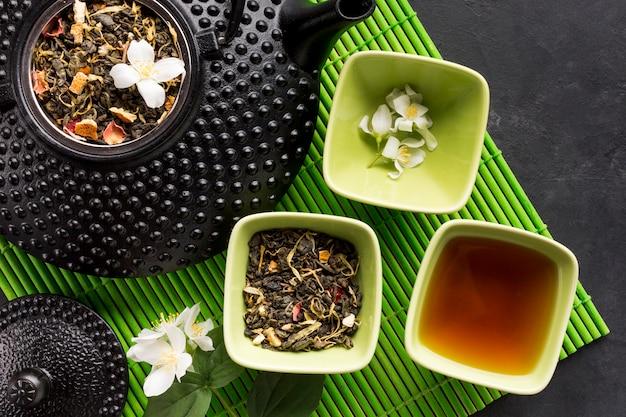 Thé aux herbes dans un bol en céramique et une théière sur un napperon vert sur fond noir Photo gratuit
