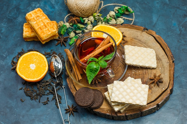 Thé Aux Herbes, Orange, épices, Biscuits, Passoire Dans Une Tasse Sur Planche De Bois Et Fond En Stuc, Pose à Plat. Photo gratuit