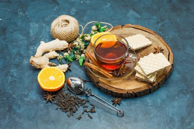 Thé Aux Herbes, Orange, épices, Gaufre, Fil, Passoire Dans Une Tasse Sur Planche De Bois Et Fond De Stuc, Pose à Plat. Photo gratuit
