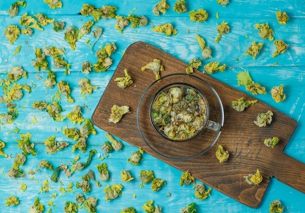 Thé Aux Herbes Séchées Dans Une Tasse En Verre Sur Bleu Et Planche à Découper, Vue Du Dessus. Photo gratuit