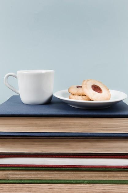 Thé et biscuits sur une pile de livres Photo gratuit