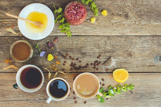 Thé, café, cacao en coupes, chicorée, citron, menthe, confiture de pétales de rose, citron vert séché, miel en vue de dessus Photo Premium