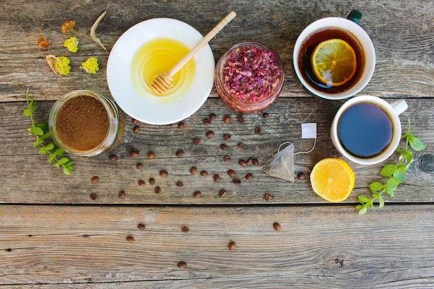 Thé, café en coupes, chicorée, citron, menthe, confiture de pétales de rose, citron vert séché, miel sur le vieux fond en bois Photo Premium