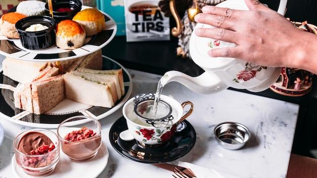 Thé chaud de bleuet de pois de papillon servi en versant de la tasse à travers l'infuseur de thé d'acier inoxydable. Photo Premium