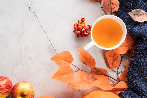 Thé chaud et feuillage d'automne sur la surface fissurée Photo gratuit