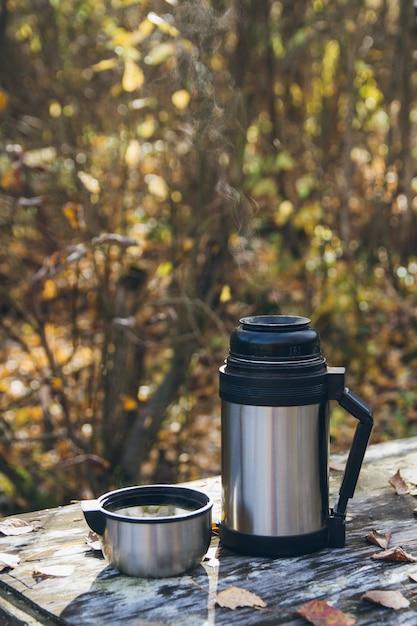 Thé chaud et un thermos sur la table à l'automne Photo Premium