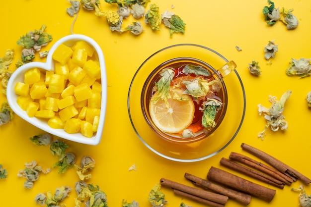 Thé Citronné Aux Herbes Séchées, Morceaux De Sucre, Bâtons De Cannelle Dans Une Tasse Sur Une Surface Jaune, à Plat. Photo gratuit