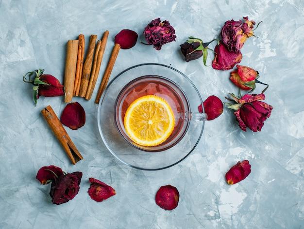 Thé Citronné Avec Des Bâtons De Cannelle, Roses Séchées Dans Une Tasse Sur Fond Bleu Grungy, Vue De Dessus. Photo gratuit
