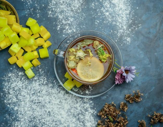 Thé Citronné Dans Une Tasse Avec Des Morceaux De Sucre, Des Herbes Séchées Vue De Dessus Sur Une Surface Bleu Grungy Photo gratuit