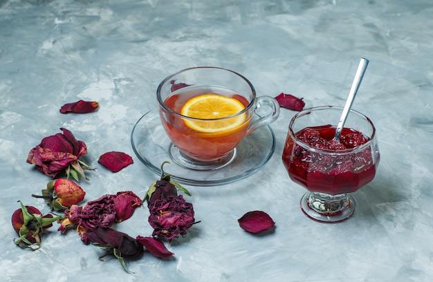 Thé à La Citronnelle Dans Une Tasse De Roses Séchées, Confiture, Cuillère Vue Grand Angle Sur Une Surface Grunge Bleu Photo gratuit