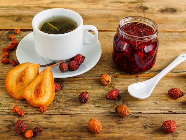Thé, Confiture Et Fruits Secs Sur Une Vieille Table En Bois. Photo Premium