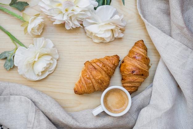 Thé avec des croissants près de belles fleurs Photo gratuit