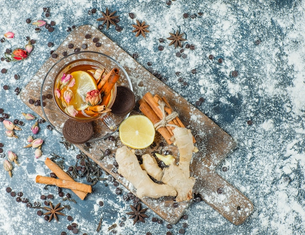 Thé Dans Une Tasse Avec Farine, Choco, Biscuits, épices, Citron, Herbes Vue De Dessus Sur Béton Et Planche à Découper Photo gratuit